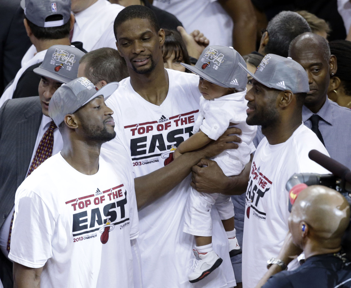 Miami Heat players Dwyane Wade, left, Chris Bosh and LeBron James talk following the presentation of the NBA Eastern Conferen