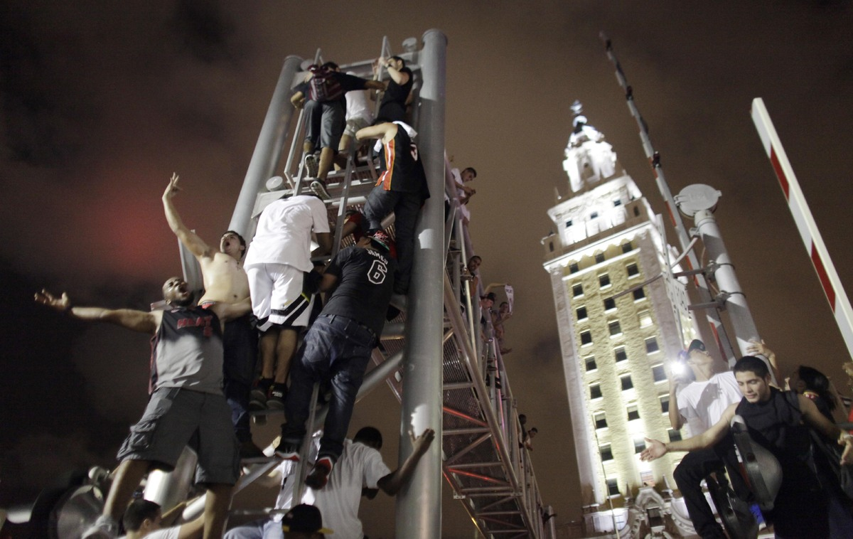 Miami Heat fans climb the sign stanchion outside American Airline Stadium while celebrating in Miami on Thursday June 20, 201
