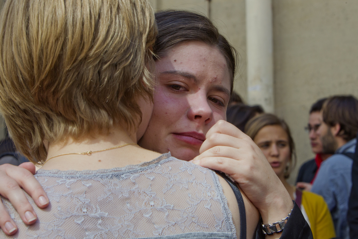 Unidentified students react in front of the Institut d'etudes Politiques, also known as Sciences Po, Thursday, June 6, 2013.