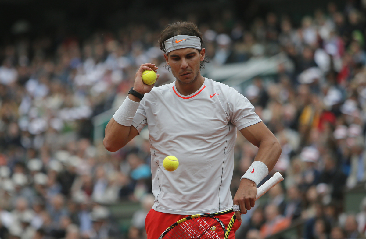 Spain's Rafael Nadal checks the balls as he plays compatriot David Ferrer during the men's final match of the French Open ten