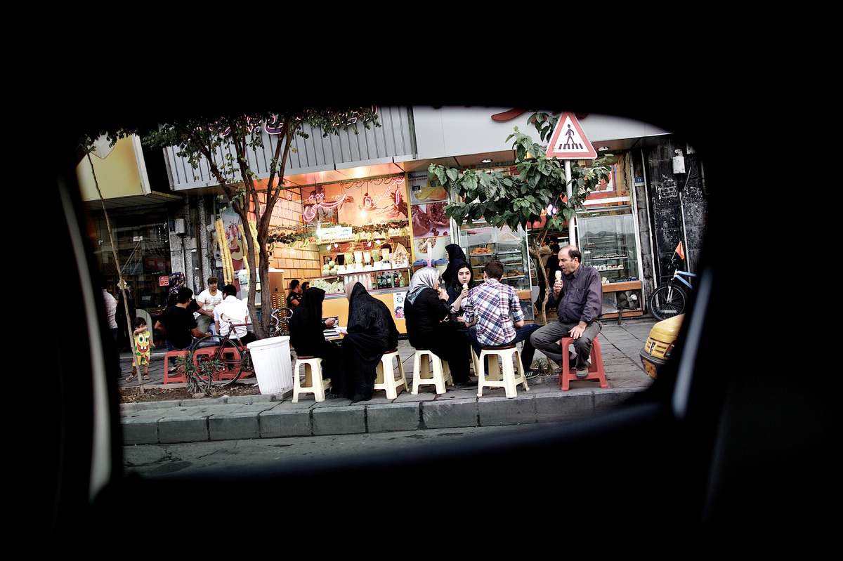 A picture taken from inside a car shows Iranians having ice cream at the historical Baharestan square in downtown Tehran on J
