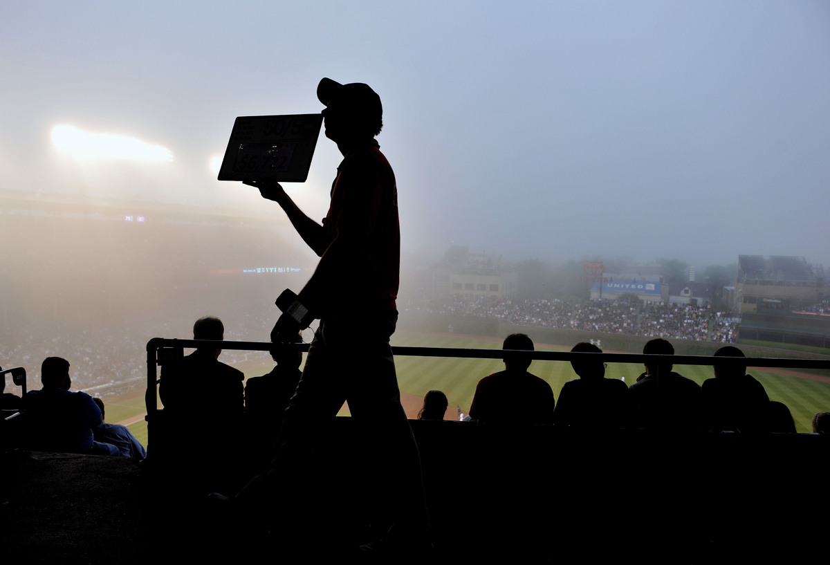 A vendor walks in the heavy fog in the upper deck of Wrigley Field during the second inning of a baseball game between the Ci