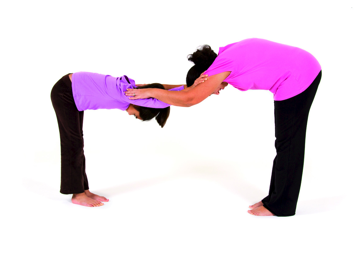"""Puppy friends"" -- a standing, partner variation of downward-facing dog -- can be done in the classroom, the yoga studio, or"