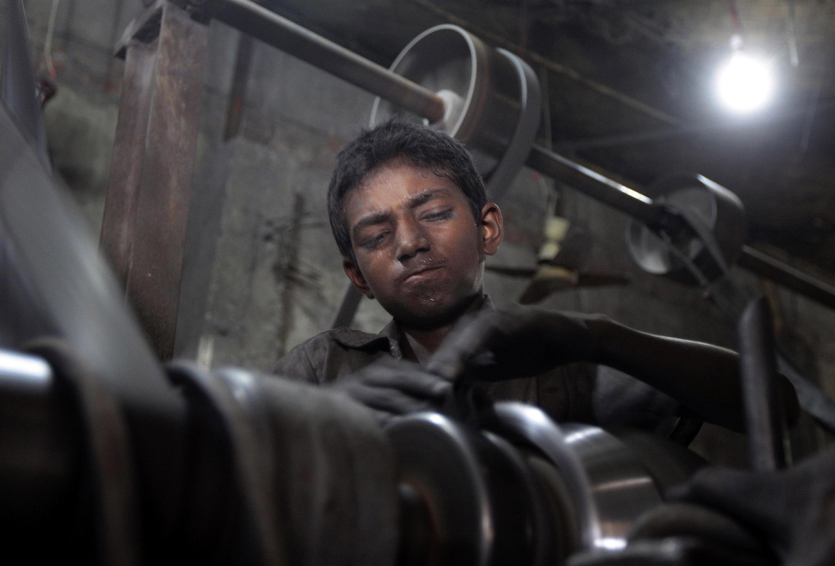 A young boy works at a metal factory in Dhaka, Bangladesh, Wednesday, June 12, 2013. The World Day Against Child Labor, which