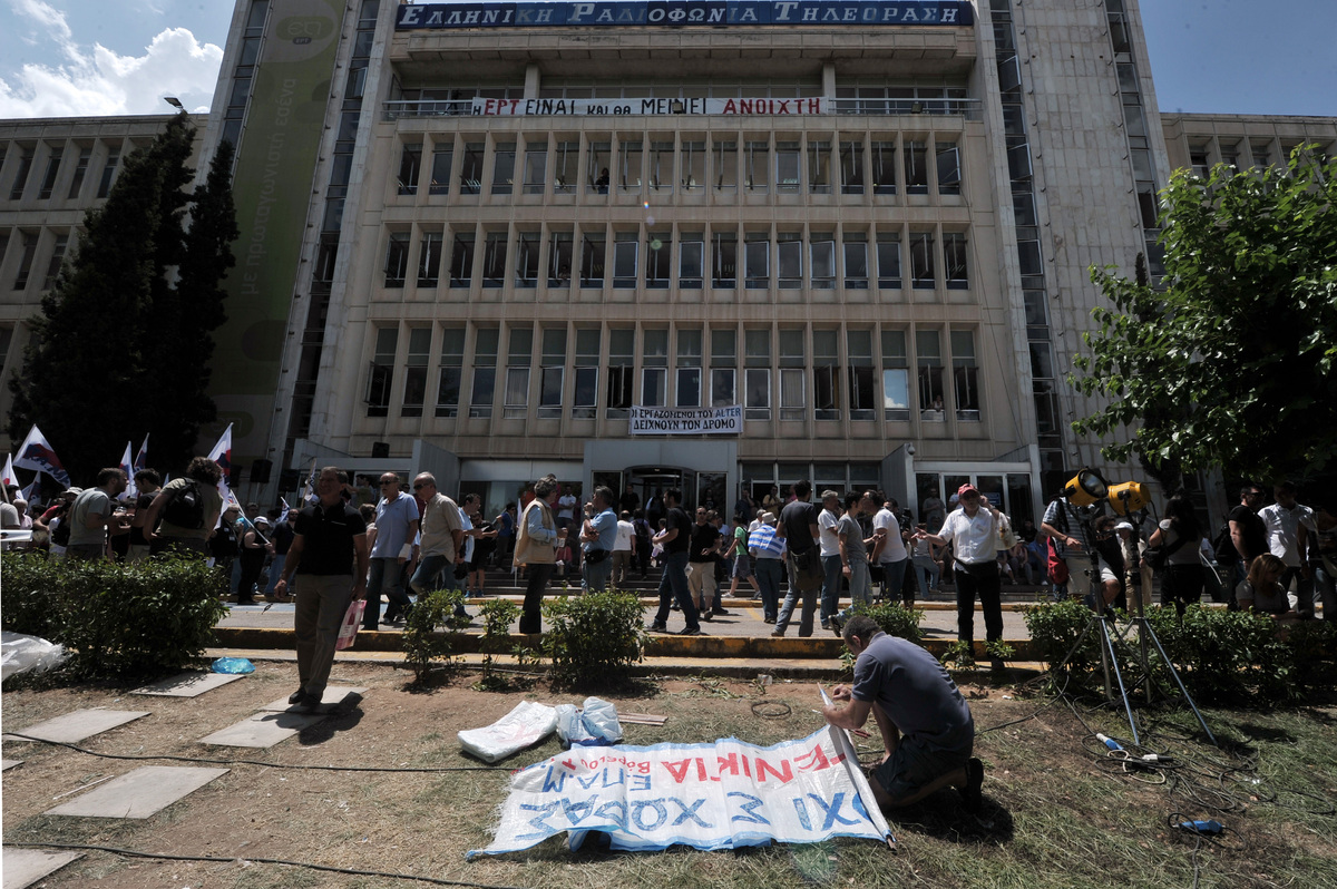 A protester prepares a banner outside the ERT state broadcaster headquarters in Athens' suburb on June 12, 2013 . Greek polit