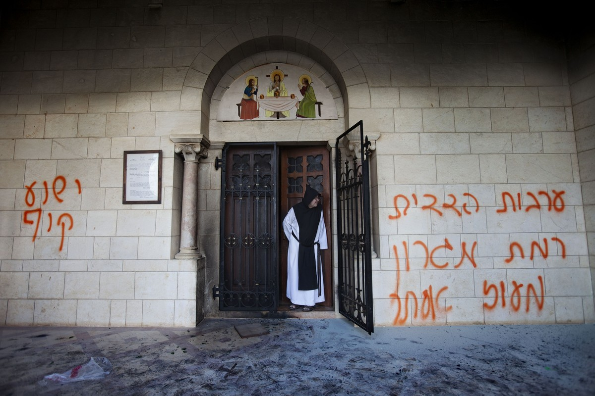 A catholic monk stands in a doorway of the Latrun Trappist Monastery where Israeli police say vandals overnight have spray-pa