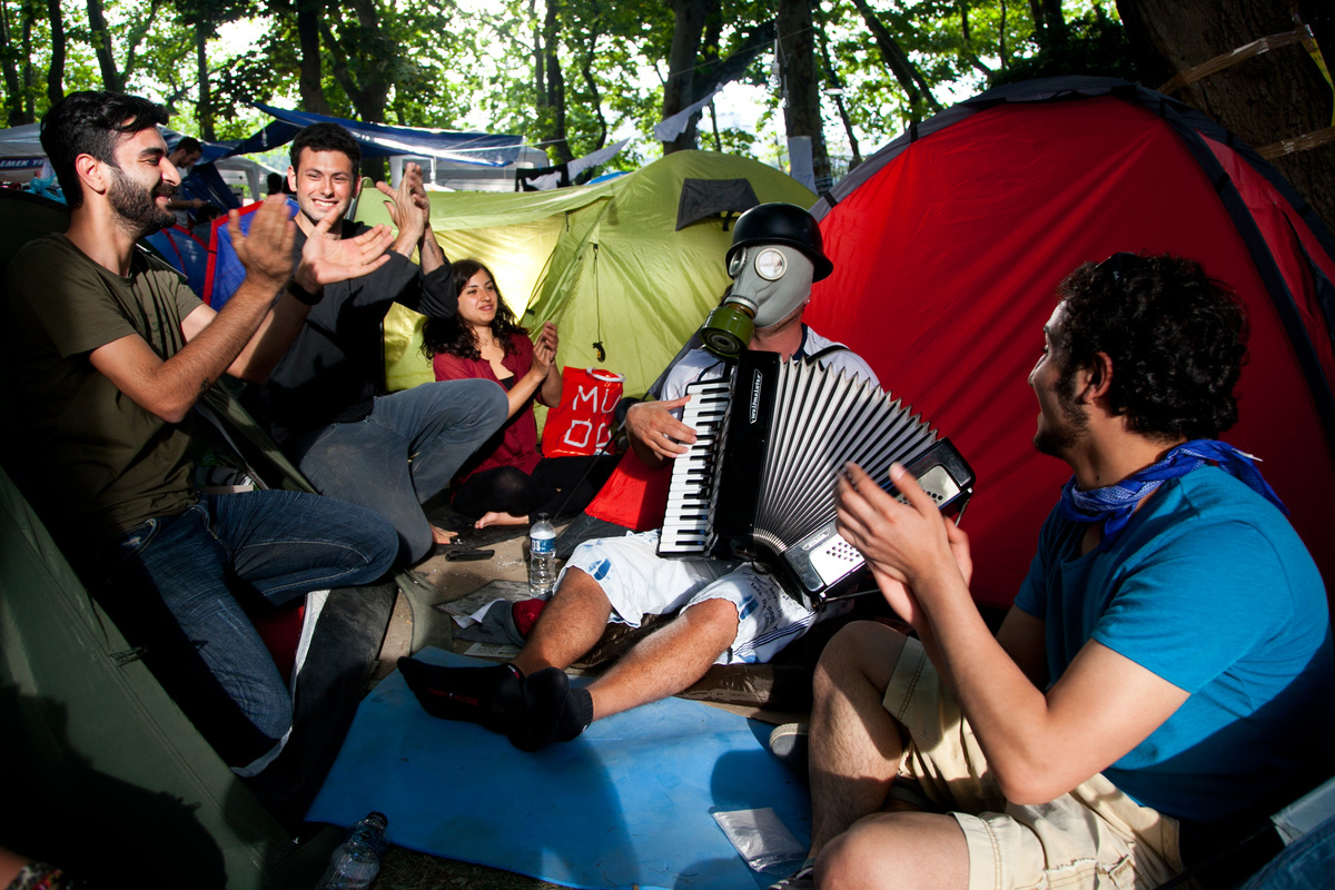 A demonstrator wearing a gas mask plays the accordeon as he sits with others near a tent at a makeshipt camp on Taksim square