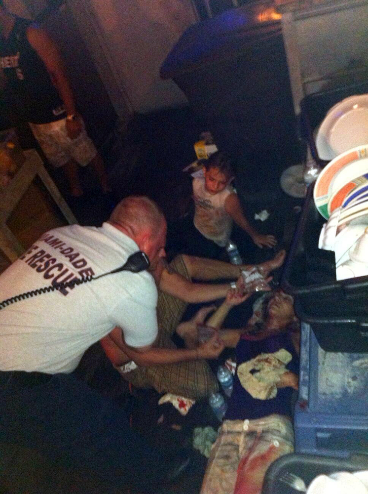 In this photo provided by WSVN-TV, victims of a deck collapse at Shuckers Bar & Grill in Miami are treated by Miami-Dade firs