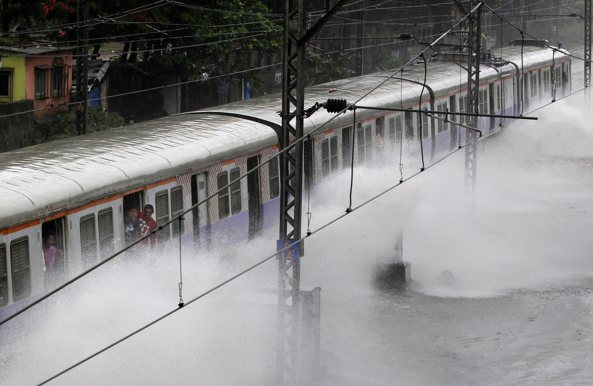 A local train moves through a flooded railway track after heavy rains in Mumbai, India, Sunday, June 16, 2013. Heavy rains co