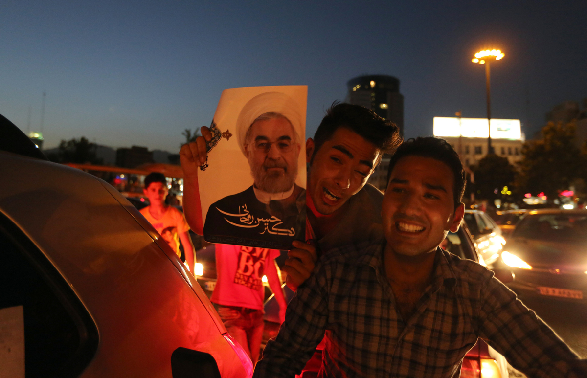 Iranians celebrate the victory of moderate presidential candidate Hassan Rouhani (portrait) in the presidential elections at