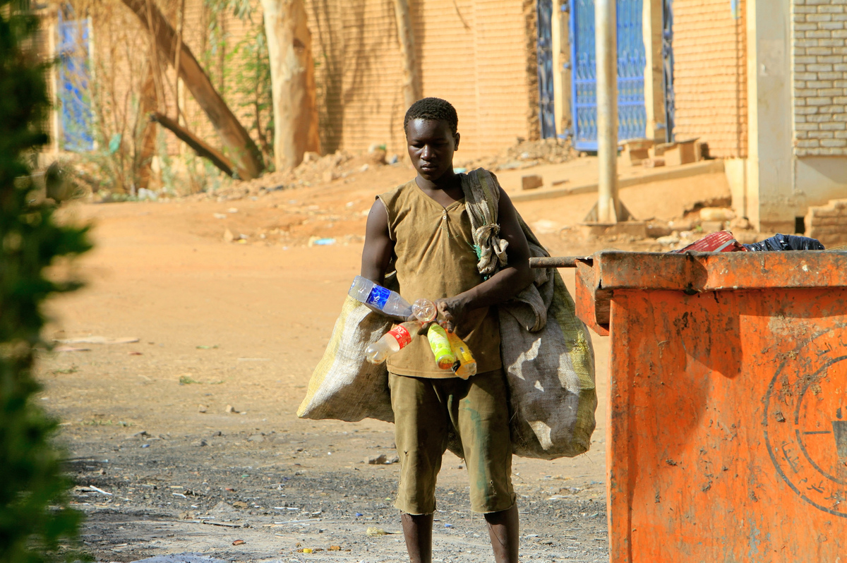 A Sudanese youth holds plastic bottles collected from a garbage container in Khartoum on June 14, 2013. An increasing number