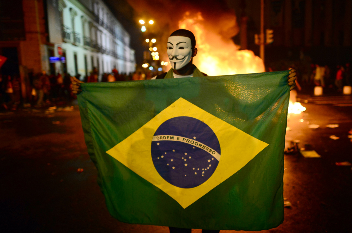 A demonstrator wearing a Guy Fawkes mask holds a Brazilian national flag during clashes in downtown Rio de Janeiro on June 17