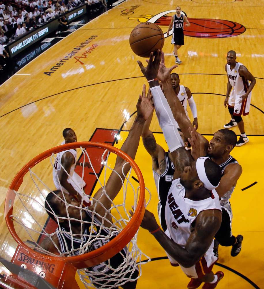 MIAMI, FL - JUNE 18:  LeBron James #6 of the Miami Heat and Tim Duncan #21 of the San Antonio Spurs go up for the ball during