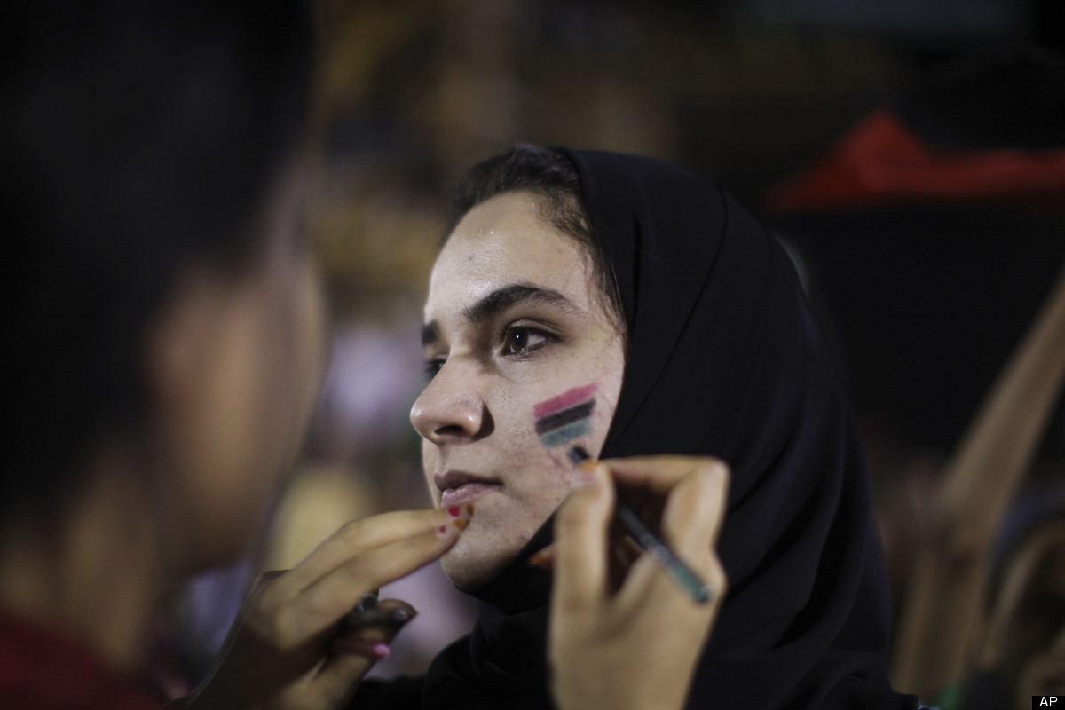 Nasgb Abd, 20, a medicine student, has her face painted with the colors of the pre-Gaddafi flag during a demonstration agains