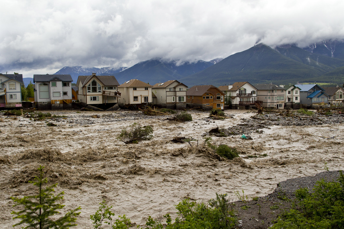 Houses damaged along the edge of Cougar Creek are shown June 20, 2013 in Canmore, Alta. Widespread flooding caused by torrent