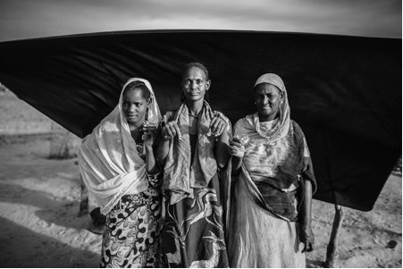 Malian refugee Mariam Diallo, 55, center, poses for a portrait with her daughter and granddaughter outside of their family's
