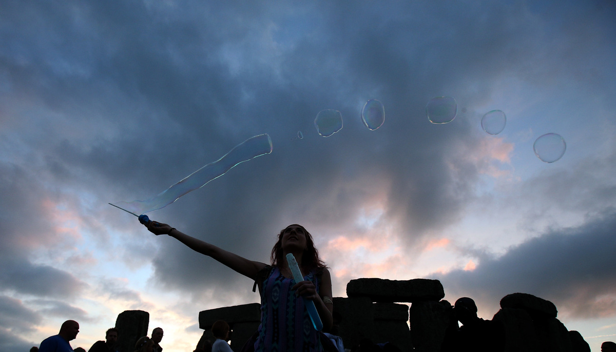 Robyn Smith makes bubbles as she waits for the arrival of the midsummer dawn at the megalithic monument of Stonehenge on June