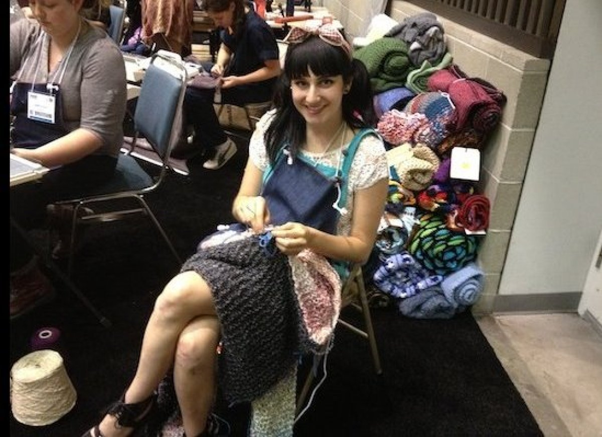 A volunteer knits a handmade blanket for a Move-in-Kit at Dwell on Design.