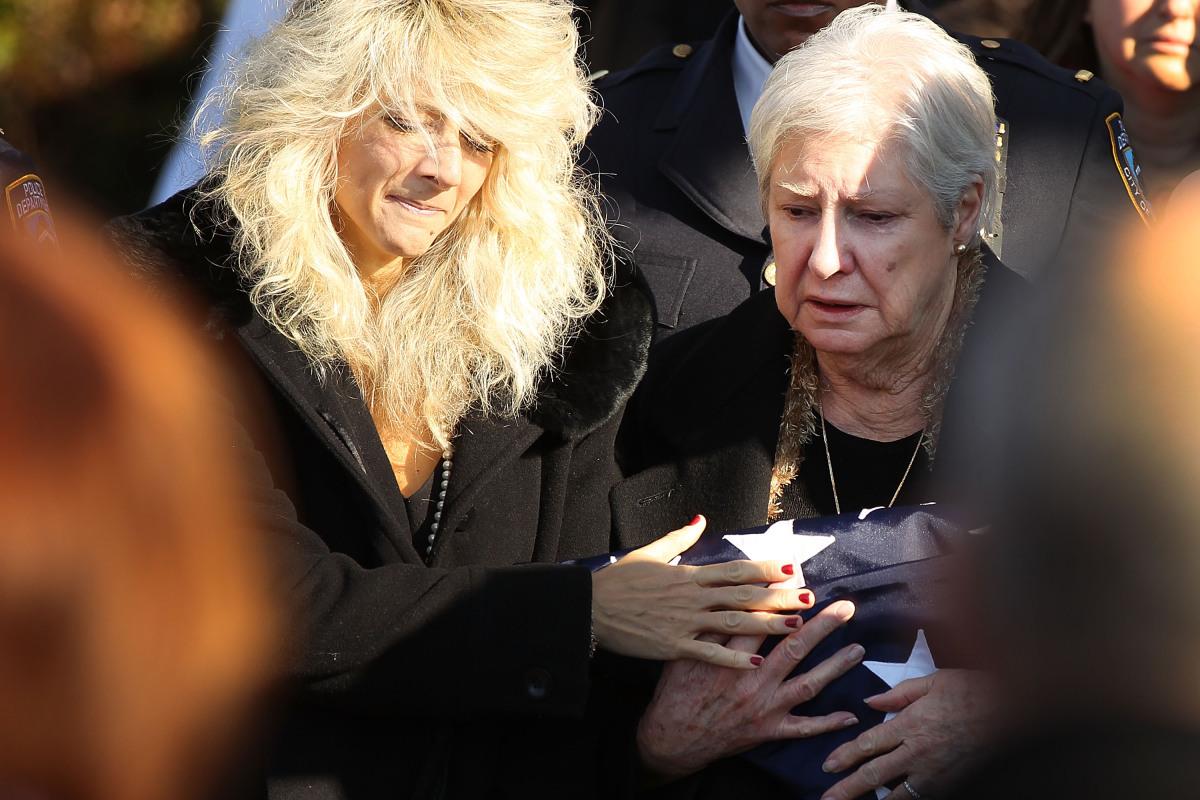 BABYLON, NY - DECEMBER 19: Paulette Figoski (L) the ex-wife of murdered NYPD officer Peter Figoski grieves alongside his moth