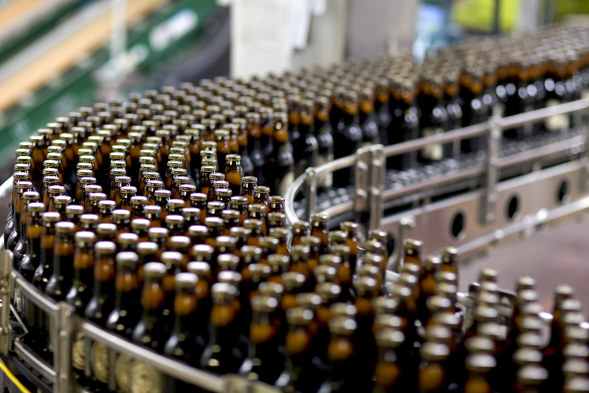 Bottles of George Killian's Irish Red beer make their way down a conveyor belt before being boxed at the brewery in Golden, C