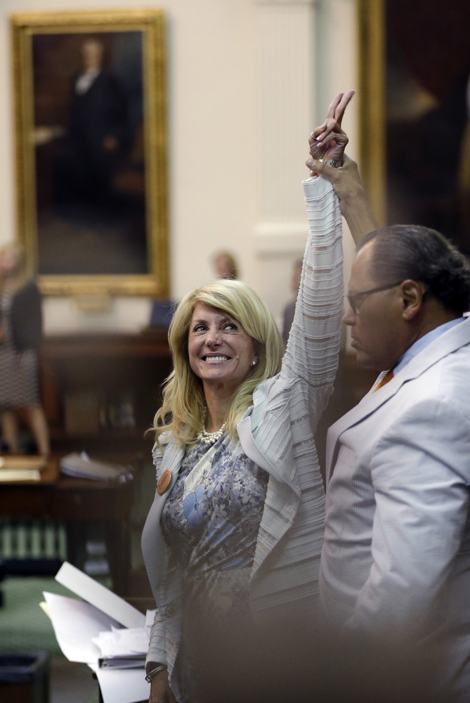 Sen. Wendy Davis, D-Fort Worth, left, who tries to filibuster an abortion bill, reacts as time expires, Tuesday, June 25, 201