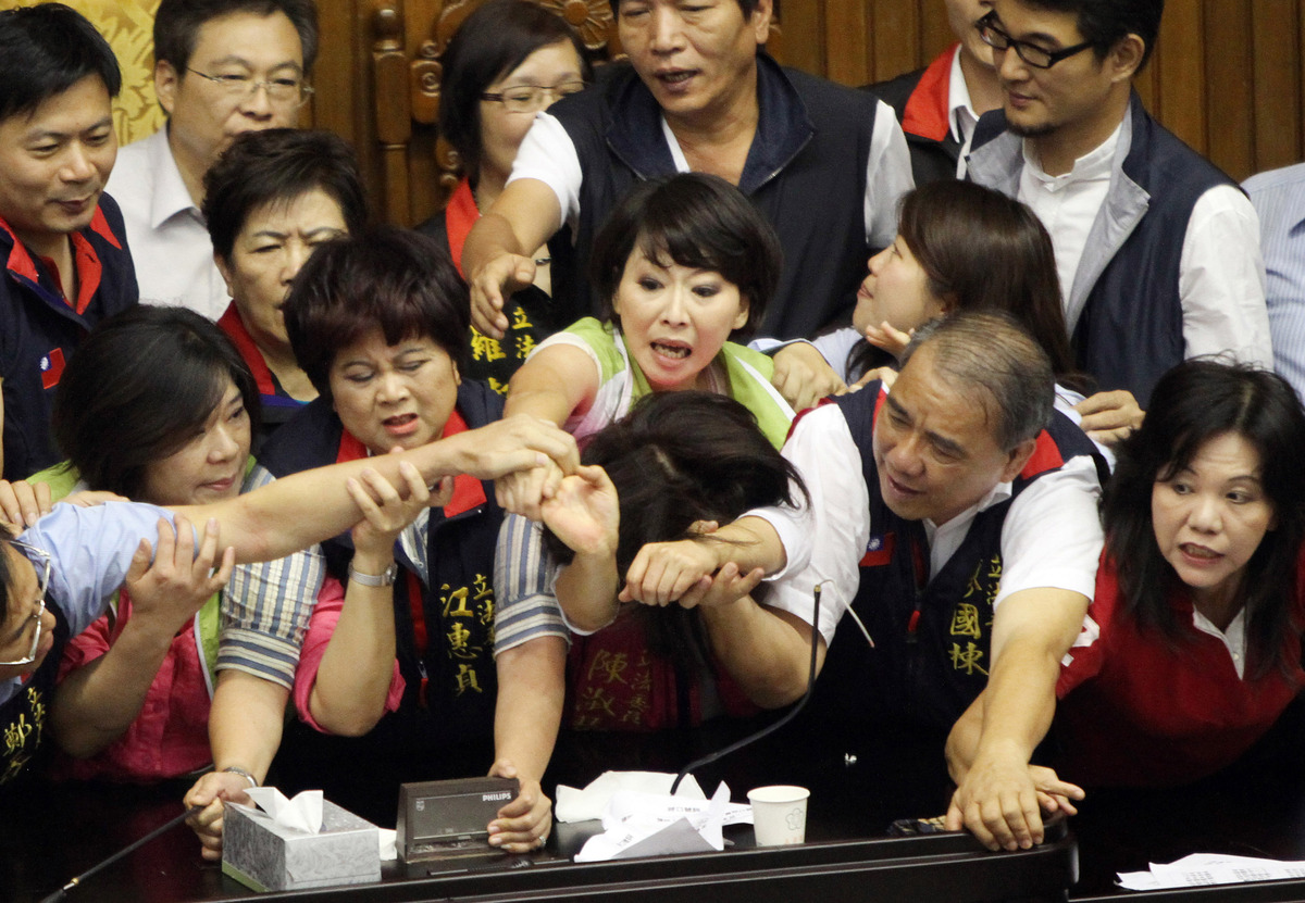 Legislators from Taiwan's ruling Kuomintang party and opposition try to seize the parliament's podium on June 25, 2013.  Figh