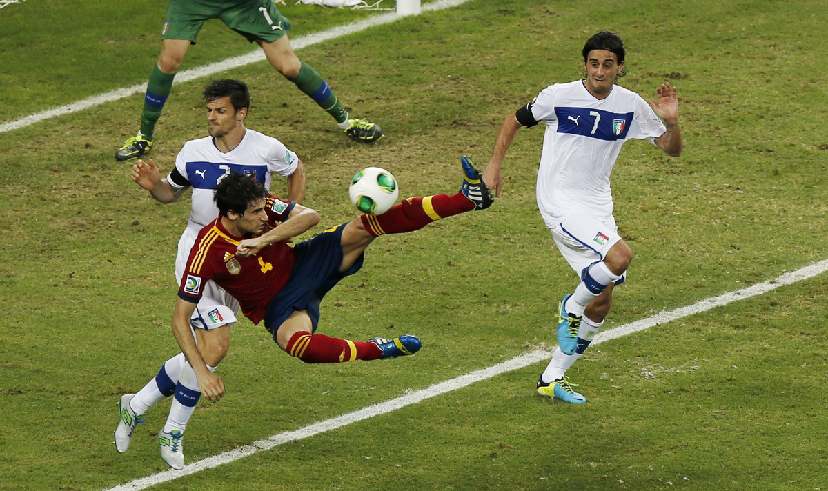 Italy's Christian Maggio, left, and Alberto Aquilani, right, challenge for the ball with Spain's Javier Martinez during the s