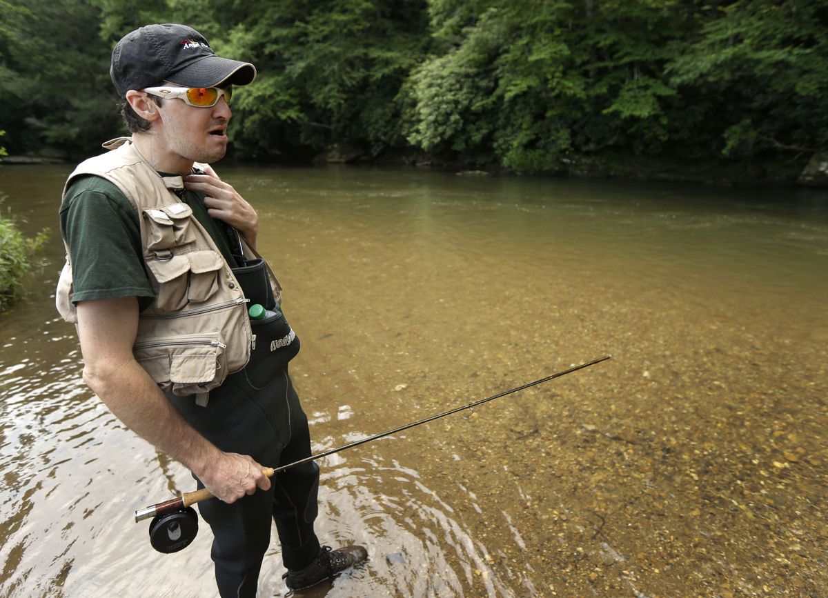In this June 25, 2013 photo, Richard Norris talks to a friend after fishing in a stream near his home in Hillsville, Va. The