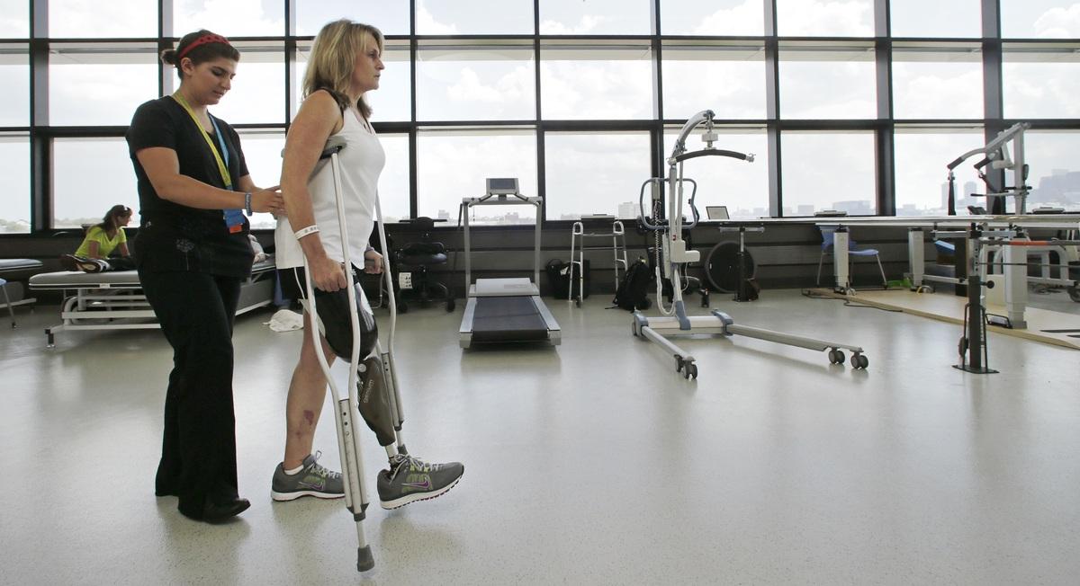 With physical therapist Dara Casparian, left, guiding her strides, Boston Marathon bombing survivor Roseann Sdoia, of Boston,