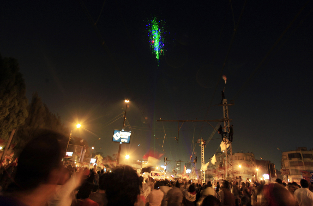 Opponents of Egypt's Islamist President Mohammed Morsi look at a military helicopter lit up by protesters' laser pointers as
