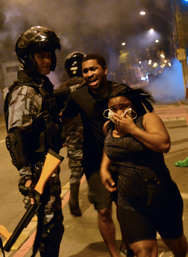 Pedestrians run past riot squad officers during a protest on a street near Maracana stadium in Rio de Janeiro, Brazil on June