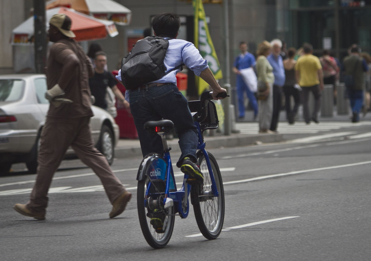 In this Tuesday, June 25, 2013, photo, a biker rides without a helmet on a Citibike, as part of New York City's bike sharing