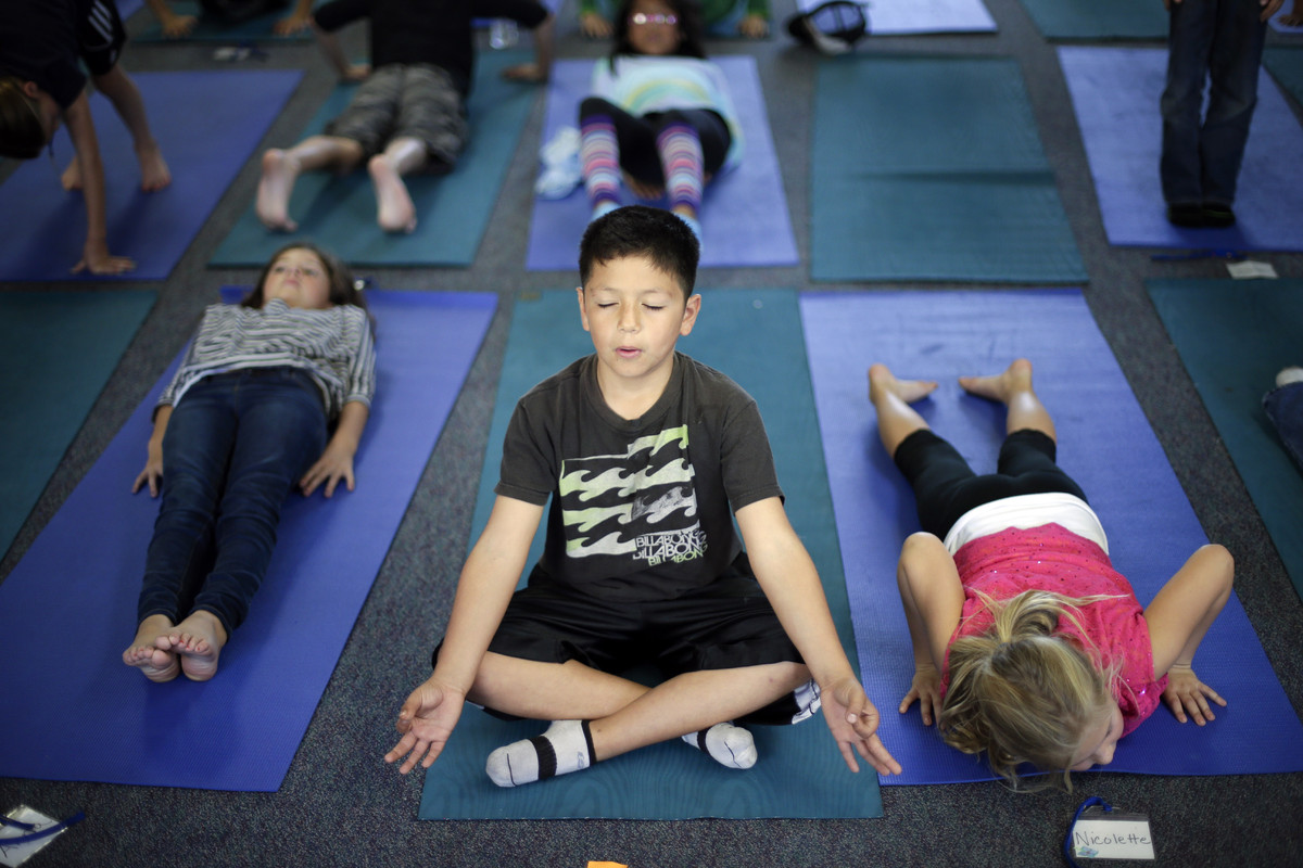 In this Dec. 11, 2012 picture, fourth grader Miguel Ruvalcaba holds a pose during a yoga class at Capri Elementary School in