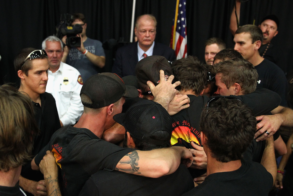 PRESCOTT, AZ - JULY 01:  Local firefighters come together and embrace after being honored at a memorial service at EmbryRiddl