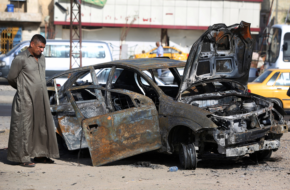 An Iraqi man inspects a burnt-out vehicle at the site of a car bomb explosion in the Hurriyah area of eastern Baghdad, on Jul