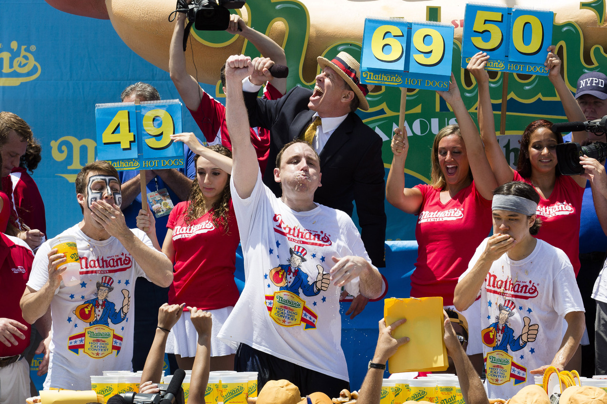 Joey Chestnut, center, wins the Nathan's Famous Fourth of July International Hot Dog Eating contest with a total of 69 hot do
