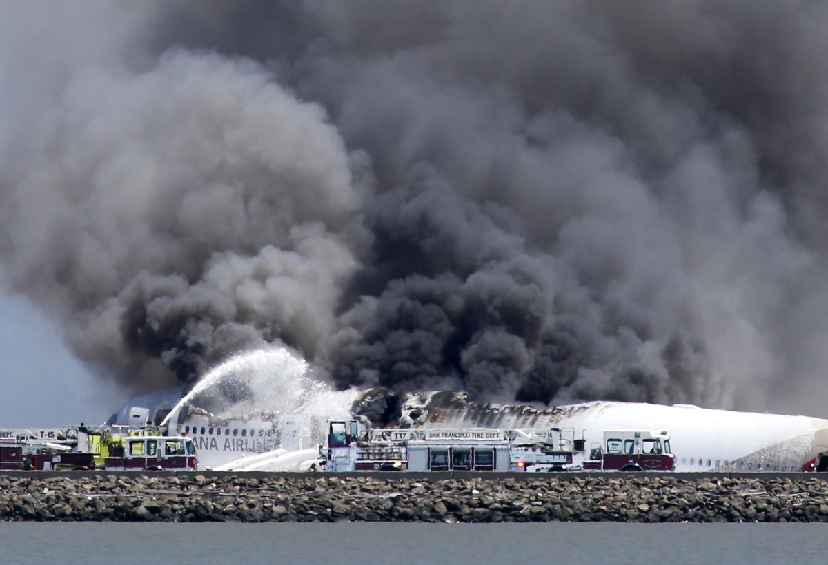 Fire crews work the crash site of Asiana Flight 214 at San Francisco International Airport in San Francisco, Saturday, July 6