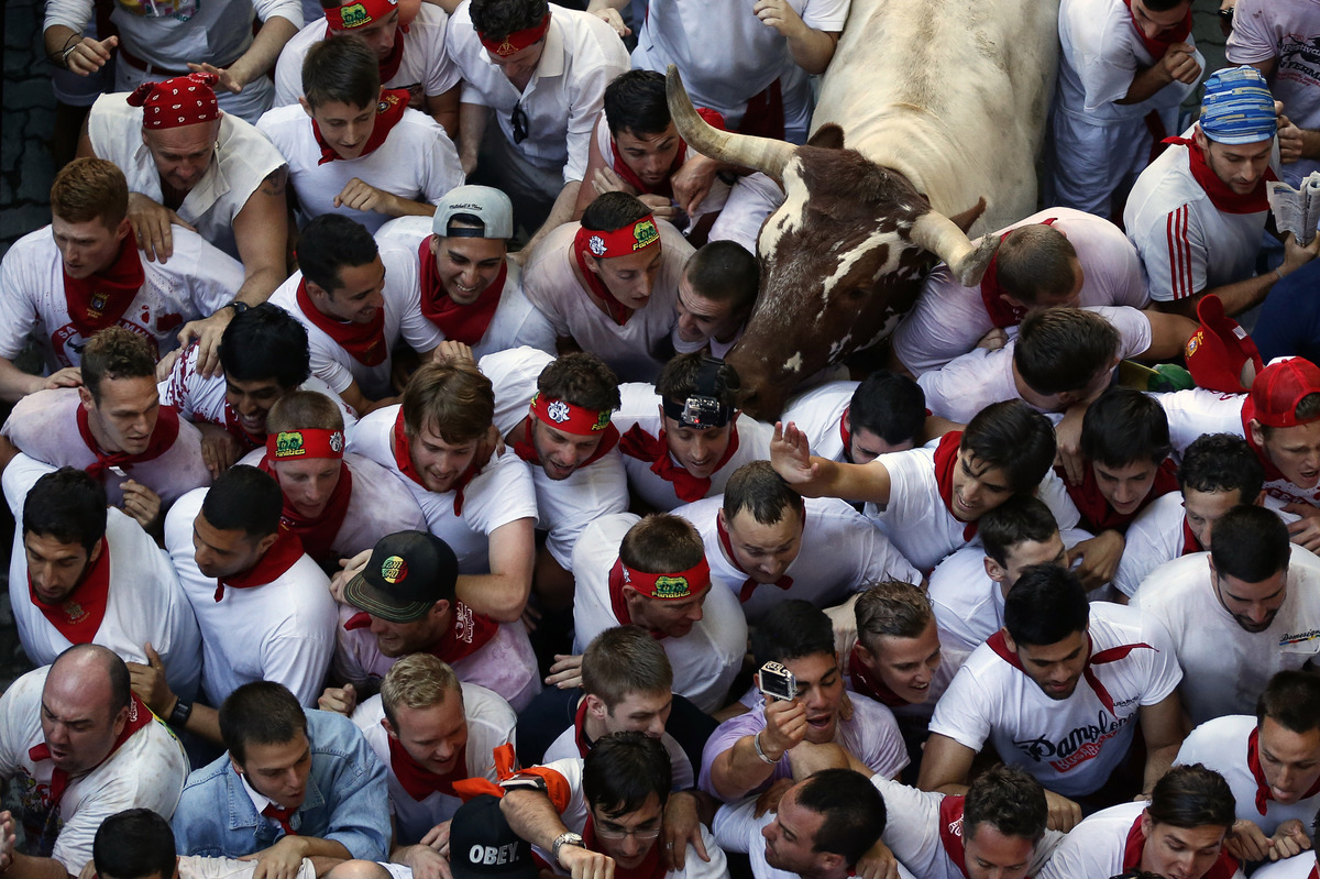 Revelers are surprised by steerers, used to drive the fighting bulls, during the running of the bulls at the San Fermin festi