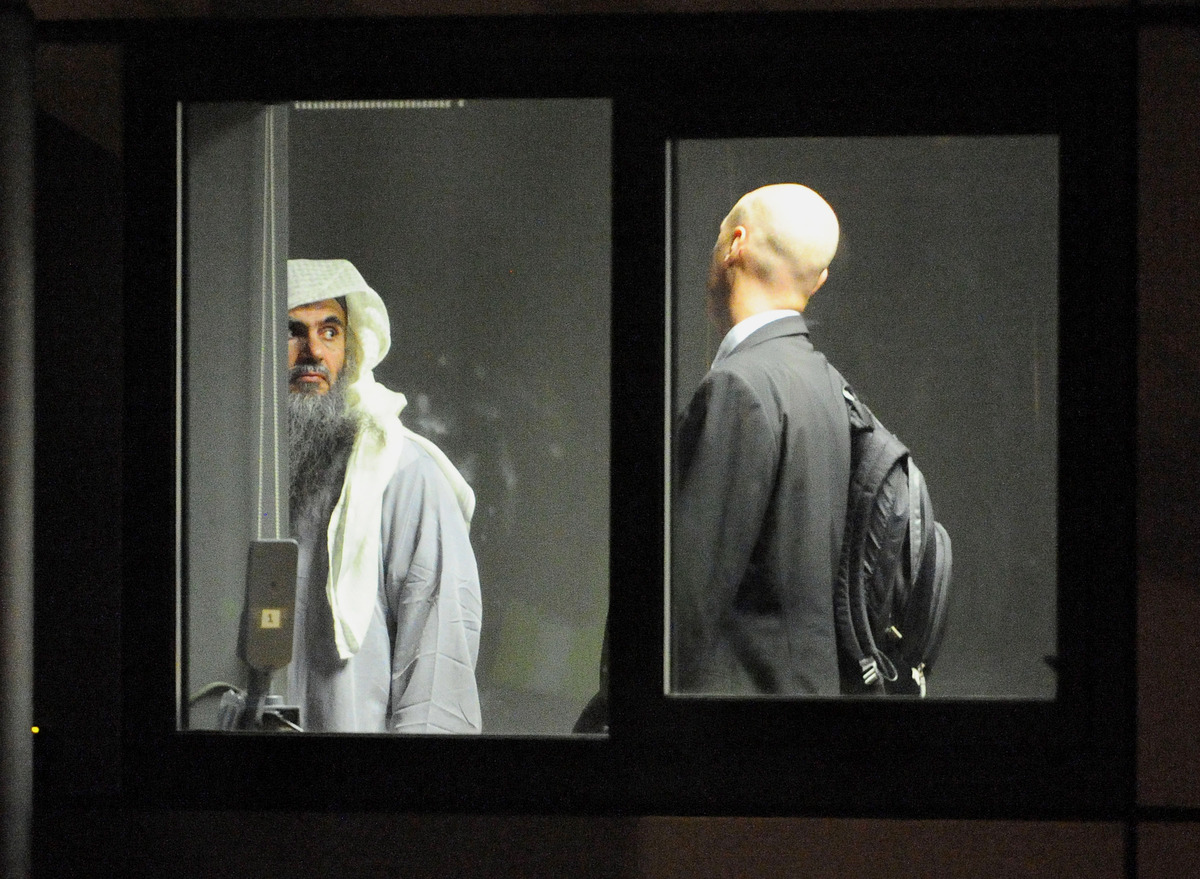 In this handout image provided by the MoD, radical cleric Abu Qatada (L) prepares to board a plane at RAF Northolt which will
