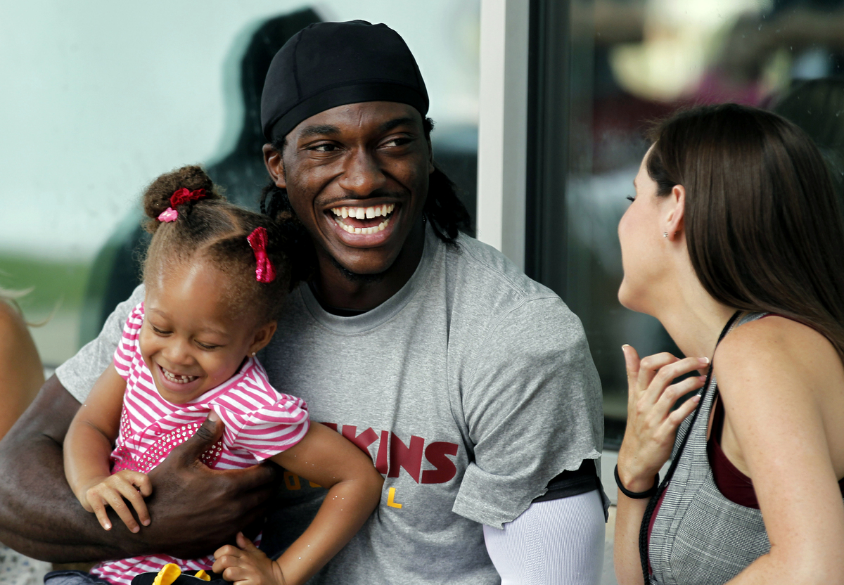Washington Redskins quarterback Robert Griffin III holds Trinity Austin, 3, a teammate's daughter, as he talks with his fianc