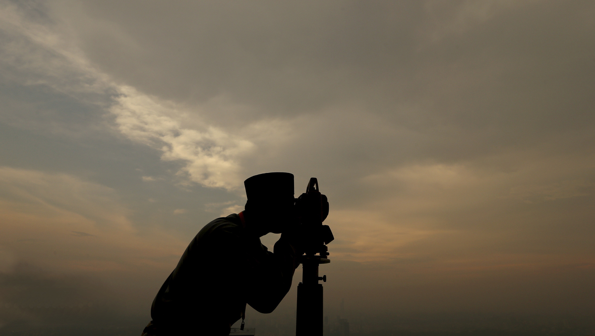 """An unidentified official of Malaysia's Islamic authority uses a telescope to perform """"Rukyah,"""" the sighting of the new moon t"""