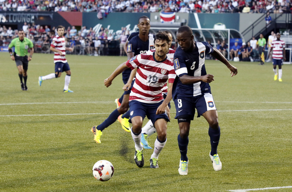 Belize's Elroy Smith, right, and United States' Chris Wondolowski chase down the ball during the first half of their CONCACAF