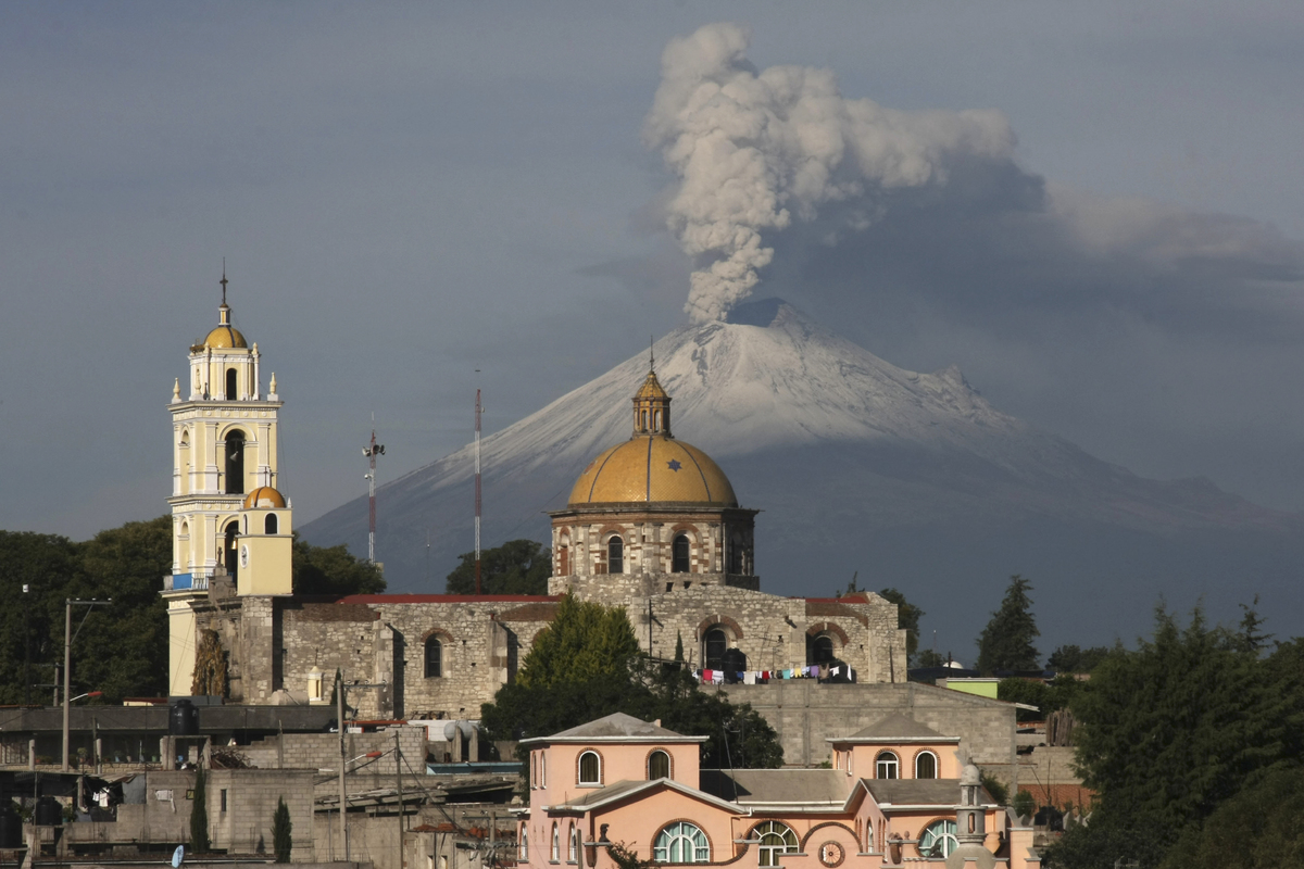 The main church in the town of San Damian Texoloc, Mexico stands in front of the Popocatepetl volcano as is spews ash and vap