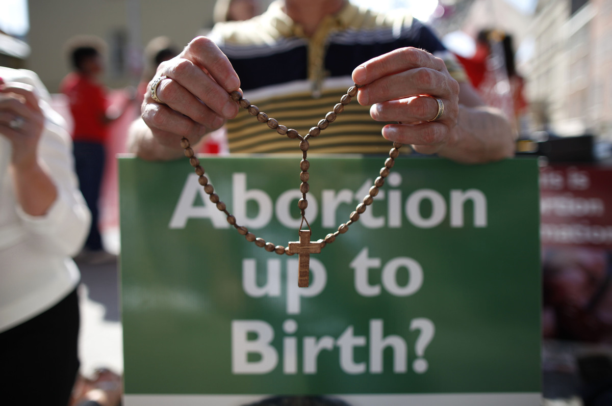 A protester holds rosary beads with a anti-abortion placard in front of the gates of the Irish Parliament building in Dublin
