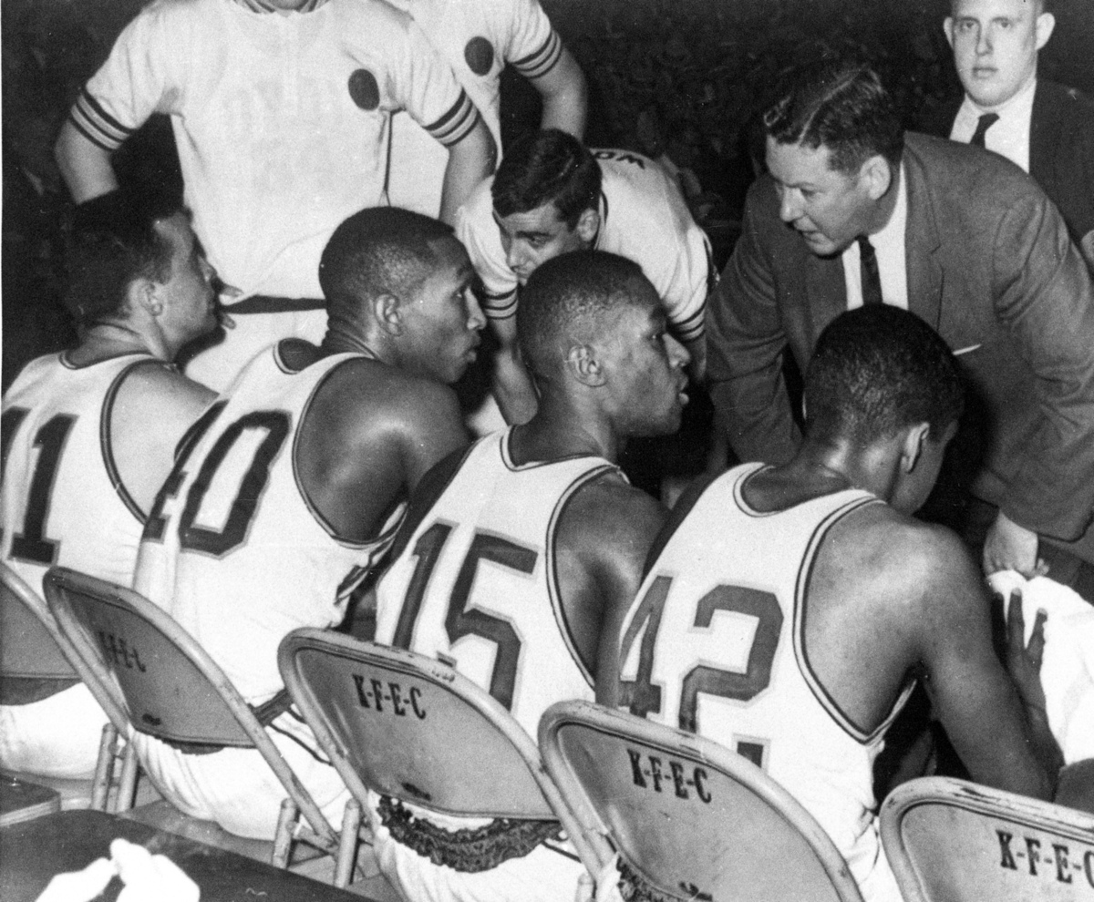 FILE - In this March 23, 1963 file photo, Loyola coach George Ireland, right, leans in to talk with his players during the fi