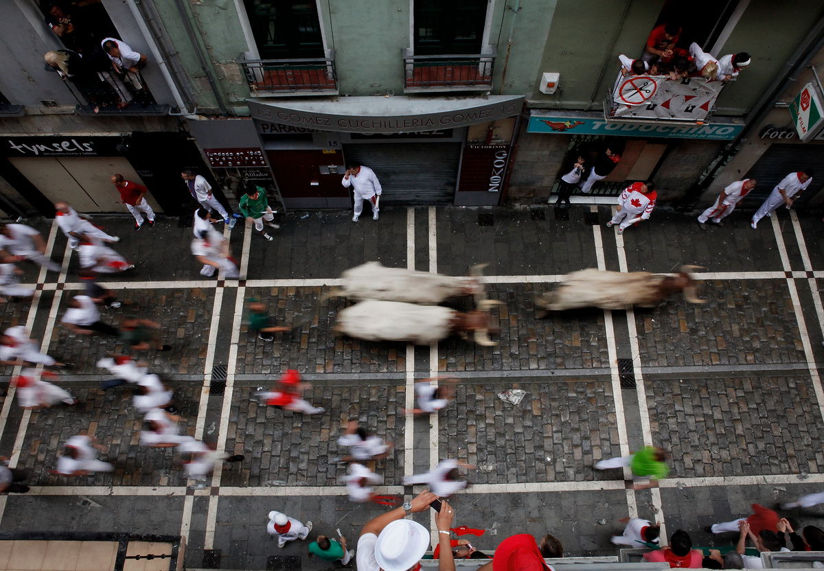 People run with bulls along Estafeta Street on the third day of the San Fermin running of the bulls on July 8, 2012 in Pamplo