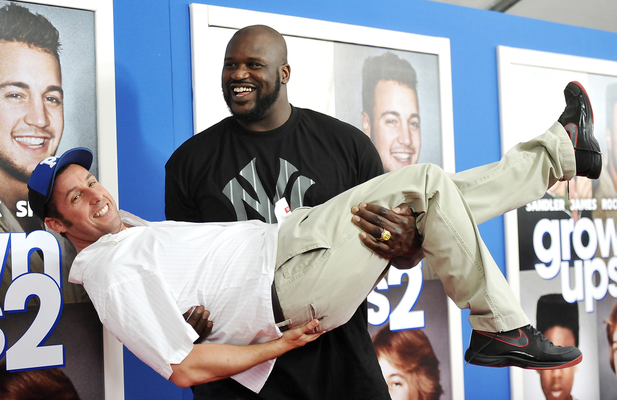"""Former professional basketball player Shaquille O'Neal gives actor Adam Sandler a lift at the premiere of """"Grown Ups 2"""" at th"""