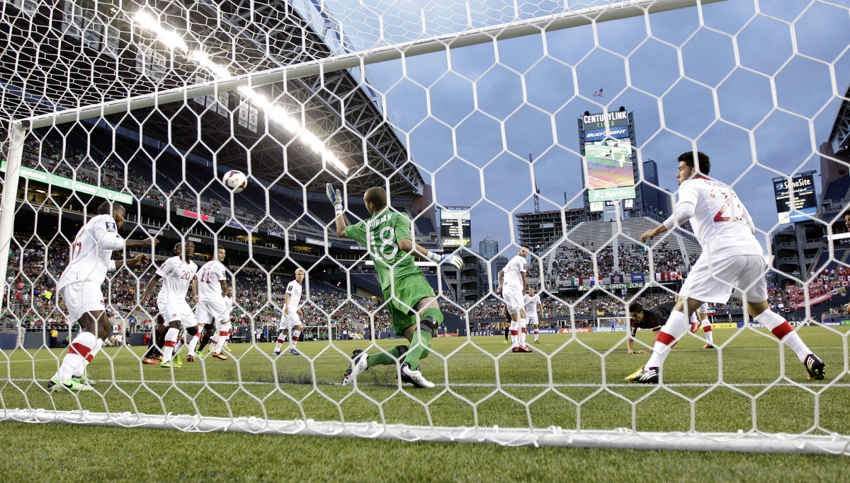 A ball headed by Mexico's Raul Jimenez gets past Canada goalkeeper Milan Borjan (18) for a goal in the first half of a CONCAC