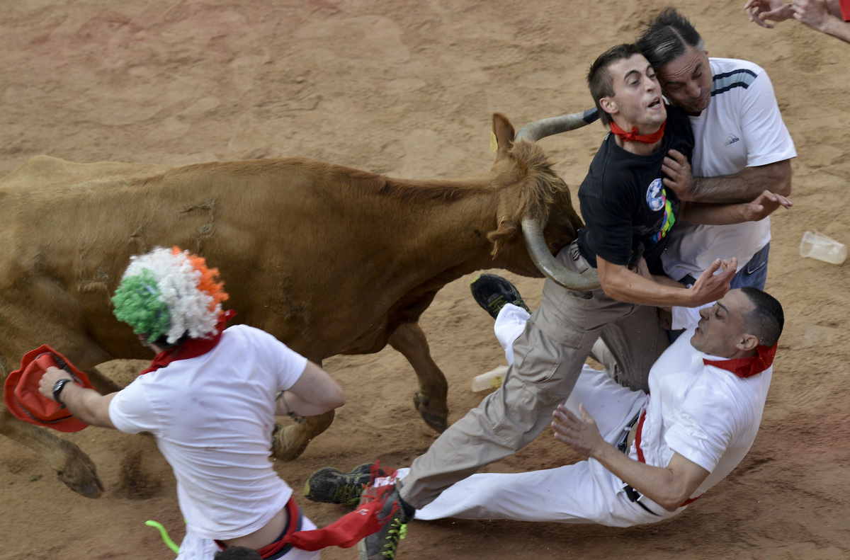 Revelers are pushed by a bull at the end of last running of the bulls at the San Fermin festival, in Pamplona Spain on Sunday