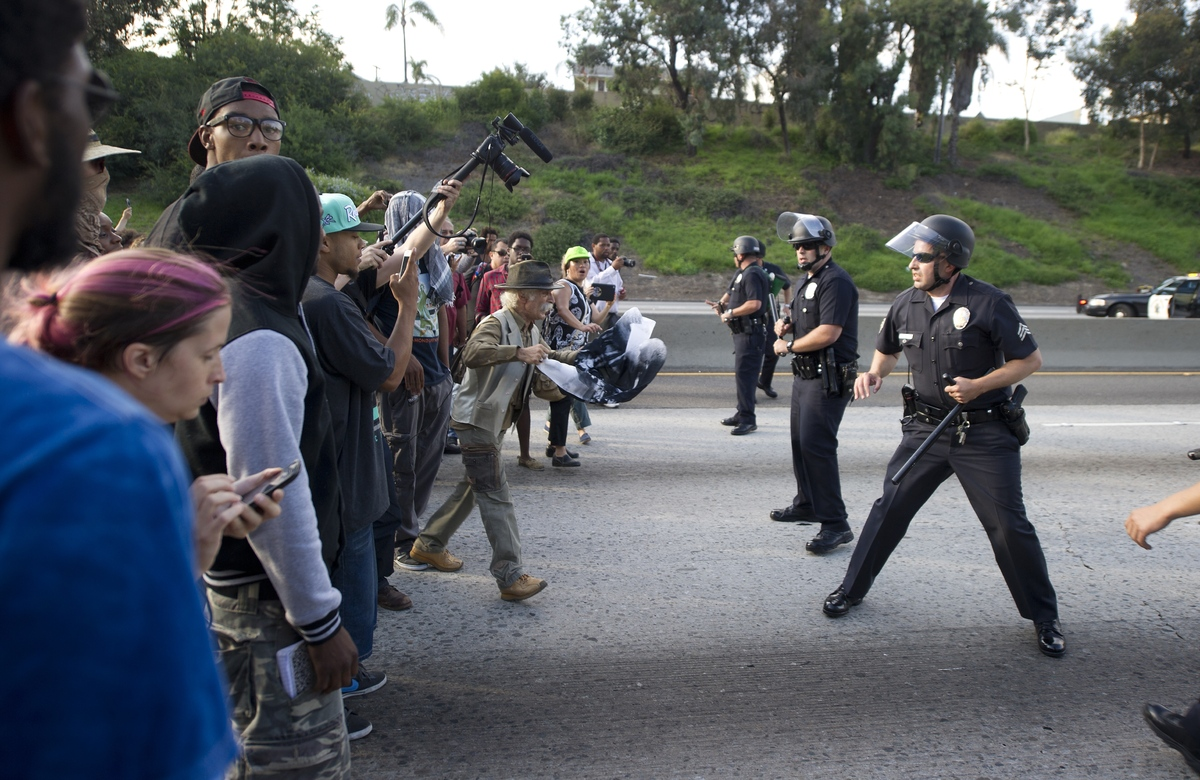 Police officers hold a line against protestors on the 10 Freeway after demonstrators angry at the acquittal of George Zimmerm